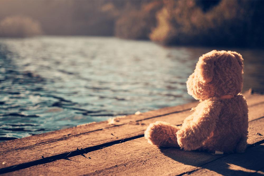 Lonely teddy bear on dock.